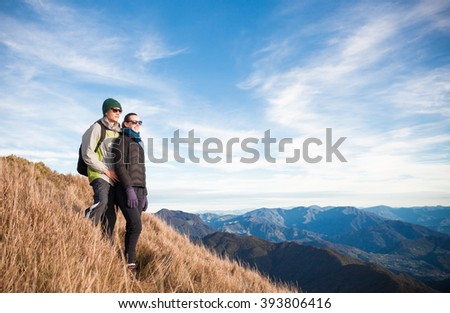 Young couple on the mountain looking over the horizon - stock photo