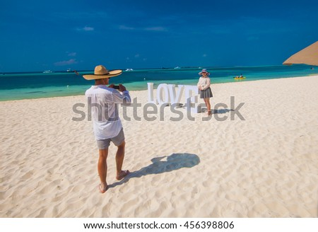 Young Couple on vacation, honeymoon, taking picture on the sandy beach - stock photo