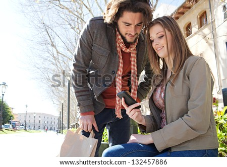 Young couple on vacation in a destination city, sitting down with shopping bags to take a break and using a smartphone device during a sunny day. - stock photo