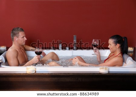 Young couple on wellness program sitting in jacuzzi bath, having red wine.? - stock photo