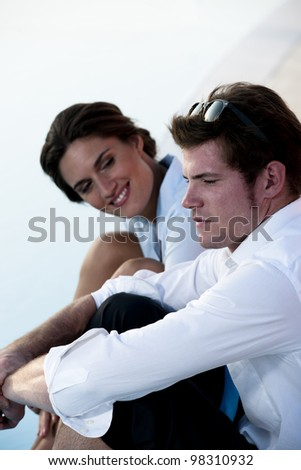 Young couple or businsspeople relaxing by pool - stock photo