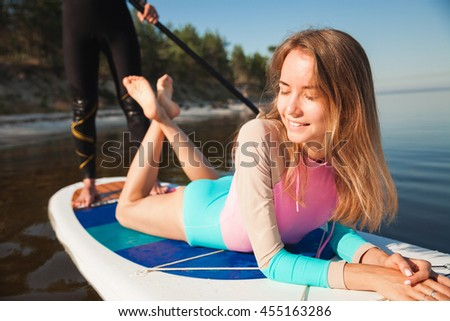 Young couple paddling on sup board with paddle. Closeup, front view, focus on woman - concept of harmony with the nature, free and healthy living, freelance, remote business. - stock photo