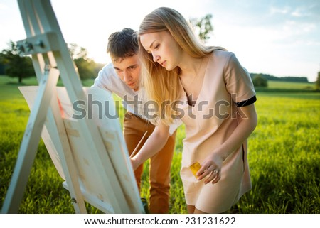 Young couple painting on an easel in a field - stock photo