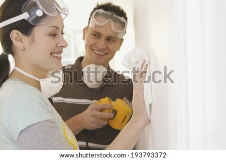 Young Couple Painting The Wall In The Apartment - stock photo