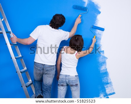Young couple painting the wall with roller together