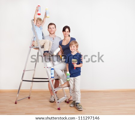 Young couple painting wall together at home - stock photo