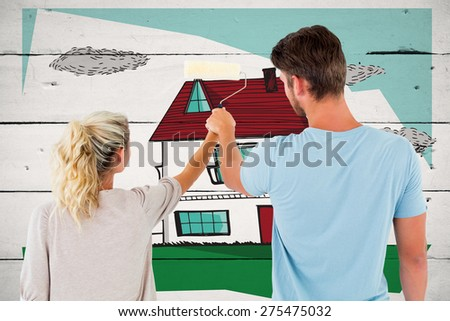 Young couple painting with roller against white wood - stock photo
