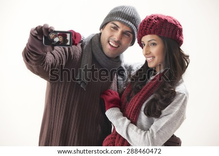 Young couple photographing themselves over white background - stock photo