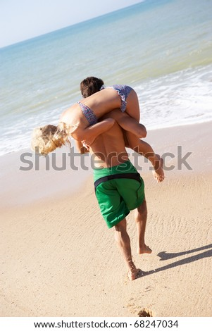 Young couple play on beach - stock photo