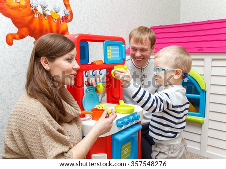 Young couple play toy kitchen with little boy