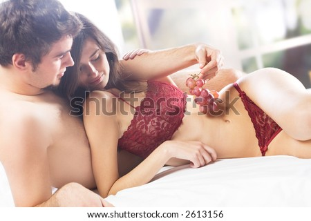 Young couple playfully eating grapes on the bed in bedroom