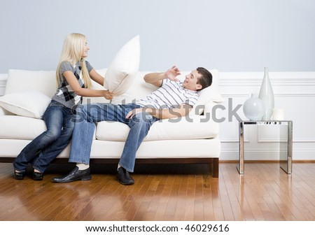 Young couple playfully have a pillow fight on a sofa.  The young man tries to avoid getting hit. Horizontal shot. - stock photo