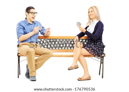 Young couple playing cards seated on wooden bench isolated on white background - stock photo