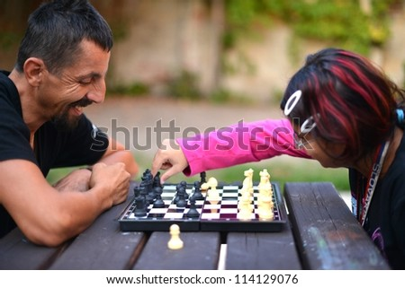 young couple playing chess - stock photo