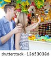 Young couple playing darts at an attractions fair ground, aiming together to win a prize, outdoors. - stock photo