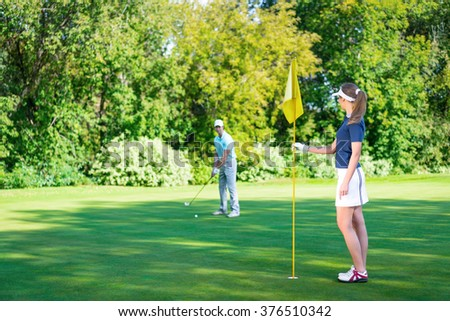 Young couple playing golf on lawn