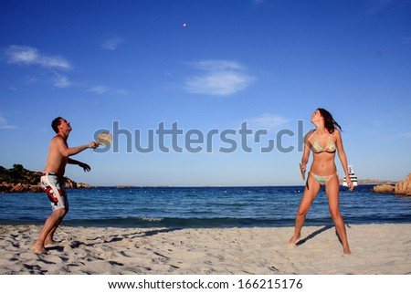 Young couple playing tennis on a beach during their vacation. - stock photo