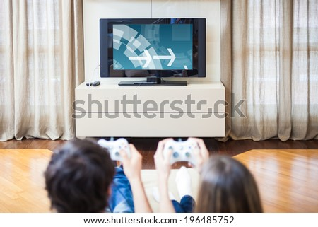 Young couple playing video games at home - stock photo