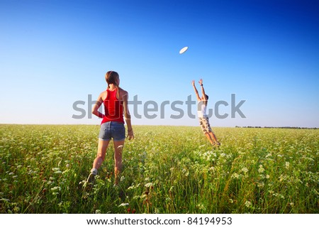 Young couple playing with disc on a green meadow with grass on clear blue sky background. Focus on a woman - stock photo