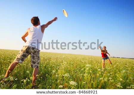 Young couple playing with disc on a green meadow with grass on clear blue sky background. Focus on a woman, man is motion blurred