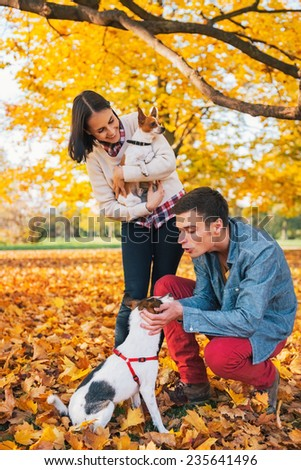 Young couple playing with dogs outdoors in autumn - stock photo