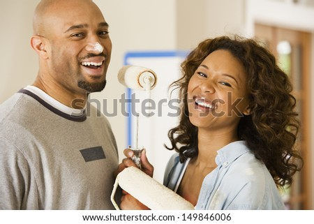 Young couple playing with paint rollers - stock photo