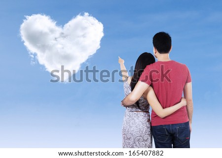 Young couple pointing at clouds shaped of heart on blue sky - stock photo