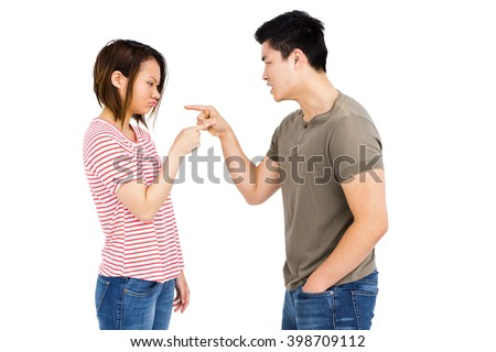 Young couple pointing at each other while having an argument on white background