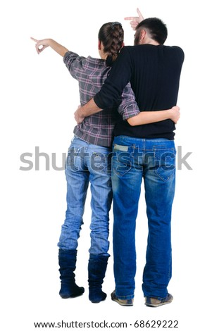 Young couple pointing at wall. Rear view. Isolated over white background.