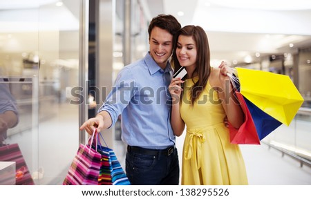 Young couple pointing at window shopping - stock photo