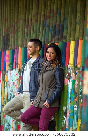 Young couple posing against colorful wooden background and smiling to camera - stock photo