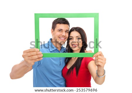 Young couple posing behind a green picture frame isolated on white background - stock photo
