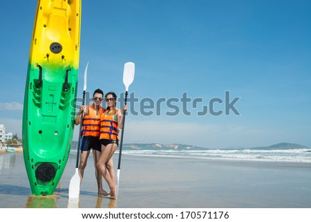 Young couple posing by kayak - stock photo