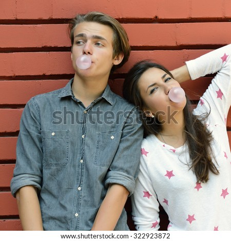 Young couple posing outdoor blowing bubbles with bubble gum against red brick wall. Urban lifestyle, happiness, joy, friends, teenage, first love concept. Image toned and noise added.