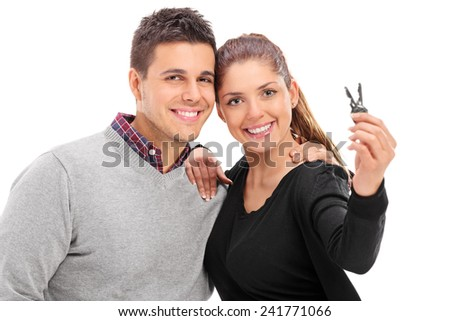 Young couple posing with a pair of door keys isolated on white background - stock photo