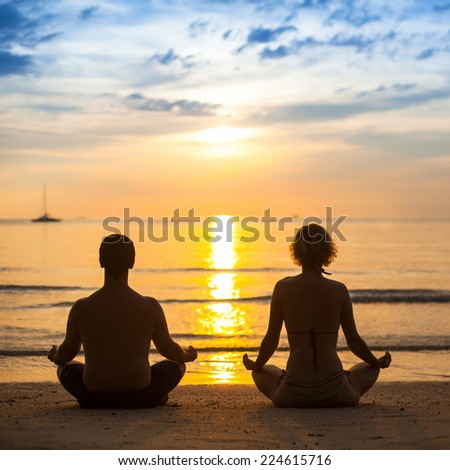 Young couple practicing yoga on sea beach during amazing sunset. - stock photo