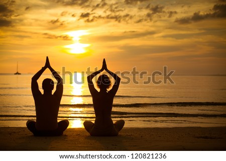 Young couple practicing yoga on the sea beach at sunset - stock photo