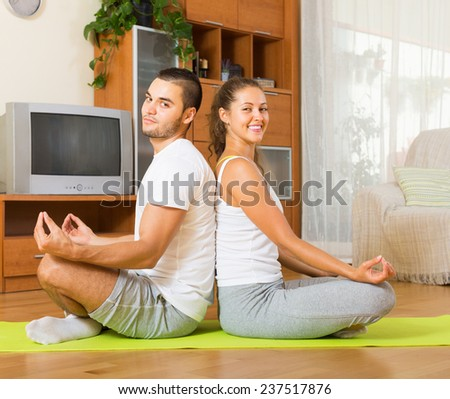 Young couple practicing yoga positions in living room - stock photo
