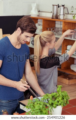 Young couple preparing a meal in their kitchen with the husband stirring the food while his wife gathers glasses and kitchenware off a shelf - stock photo