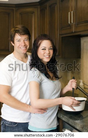 Young couple preparing food in their kitchen - stock photo