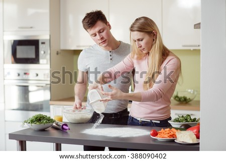 Young couple preparing the pizza in the kitchen. Young man and blond hair woman relaxing and having fun with cooking. - stock photo