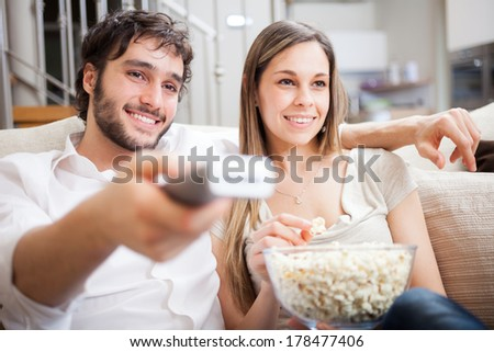 Young couple preparing to watch a movie - stock photo