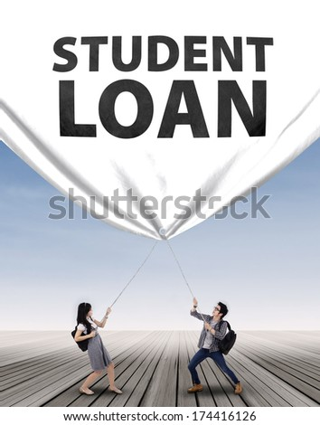Young couple pulling a big banner of student loan - stock photo