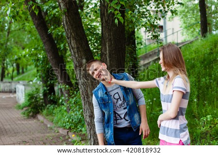 Young couple quarreling outdoors. angry woman girl giving slap to her boyfriend. slapping across  - stock photo