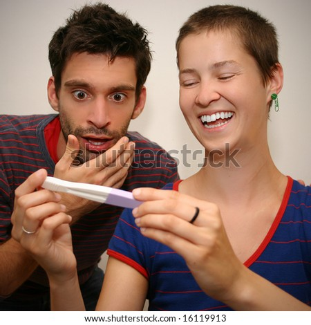 young couple reacting differently about the results of a pregnancy test - stock photo
