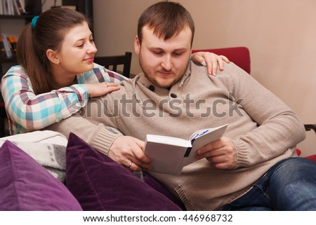 young couple reading a  book at home together