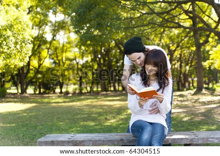young couple reading a book on park bench - stock photo