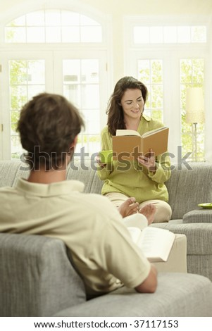 Young  couple reading book sitting at home on couch. Selective focus on women.