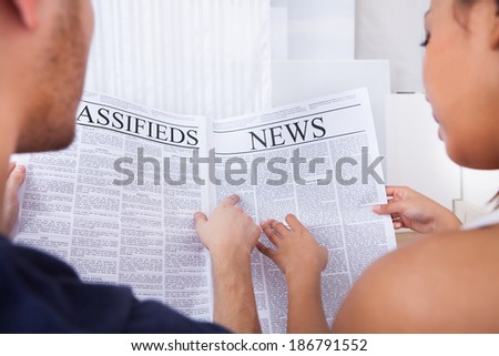 Young couple reading newspaper together on sofa at home - stock photo