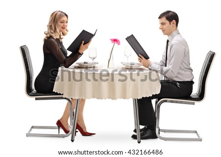 Young couple reading the menu and sitting at a restaurant on a date isolated on white background - stock photo